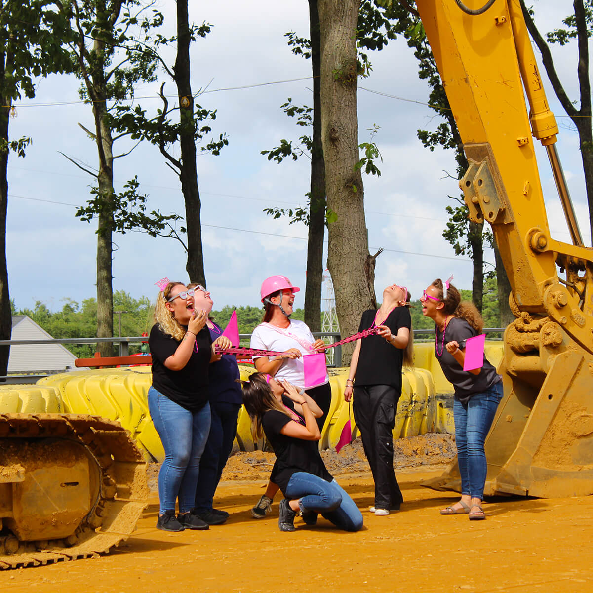 Bachelorette party having fun by excavator